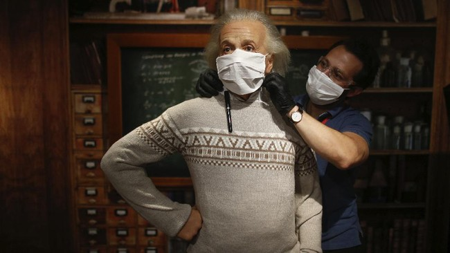In order to raise awareness against the spread of the coronavirus, a worker at Madame Tussauds attraction in Istanbul, places a mask on the wax figure of Albert Einstein during a photo-op, Saturday, July 11, 2020. Turkish authorities have made the wearing of masks mandatory in most of the country to curb the spread of COVID-19 following an uptick in confirmed cases since the reopening of many businesses. (AP Photo/Emrah Gurel)
