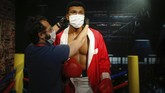 In order to raise awareness against the spread of the coronavirus, a worker at Madame Tussauds attraction in Istanbul, places a mask on the wax figure of Muhammad Ali during a photo-op, Saturday, July 11, 2020. Turkish authorities have made the wearing of masks mandatory in most of the country to curb the spread of COVID-19 following an uptick in confirmed cases since the reopening of many businesses. (AP Photo/Emrah Gurel)