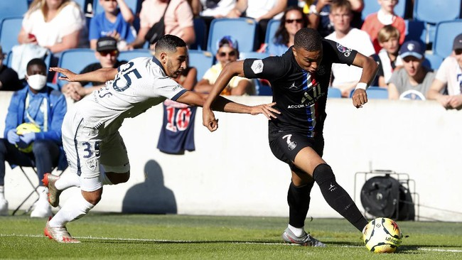 Paris Saint Germain's Kylian Mbappe, right, challenges for the ball with Elies Mahmoud of Le Havre AC during a friendly soccer match between Paris Saint Germain and Le Havre, in Le Havre, western France, Sunday, July 12, 2020. (AP Photo/Thibault Camus)