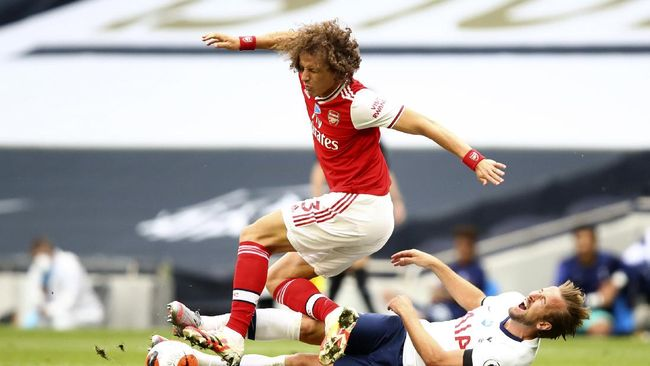 Tottenham's Harry Kane, on the ground, fights for the ball with Arsenal's David Luiz during the English Premier League soccer match between Tottenham Hotspur and Arsenal at the Tottenham Hotspur Stadium in London, England, Sunday, July 12, 2020. (Julian Finney/Pool via AP)
