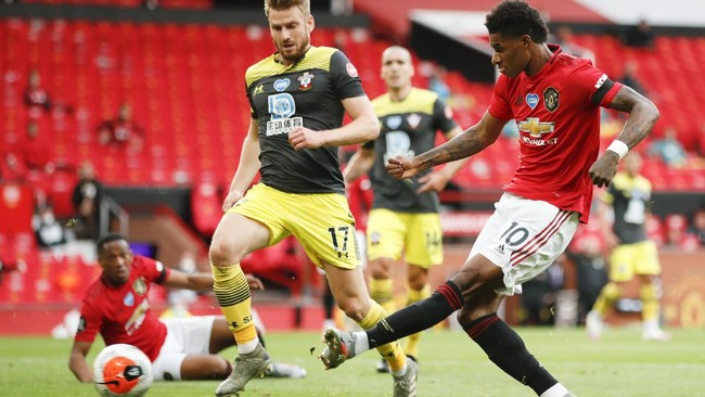 Manchester United's Marcus Rashford, right, scores his team's first goal during the English Premier League soccer match between Manchester United and Southampton at Old Trafford in Manchester, England, Monday, July 13, 2020. (AP Photo/Clive Brunskill,Pool)