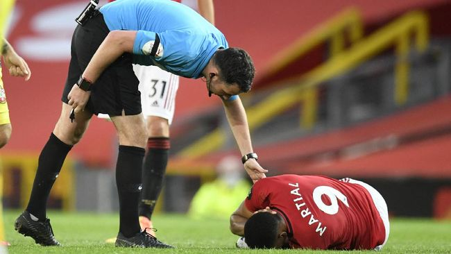 Referee Chris Kavanagh checks on Manchester United's Anthony Martial during the English Premier League soccer match between Manchester United and Southampton at Old Trafford in Manchester, England, Monday, July 13, 2020. (AP Photo/Peter Powell,Pool)