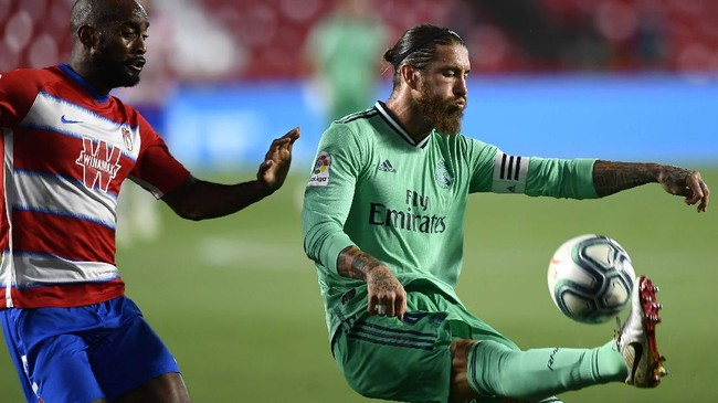 Real Madrid's Sergio Ramos, right, controls the ball with Granada's Dimitri Foulquier during the Spanish La Liga soccer match between Granada and Real Madrid at the Los Carmenes stadium in Granada, Spain, Monday, July 13, 2020. (AP Photo/Jose Breton)