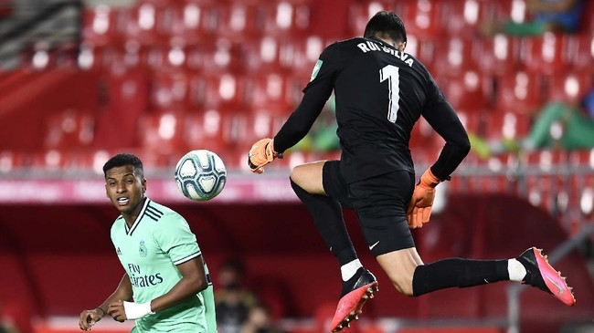 Real Madrid's Rodrygo, left, vies for the ball with Granada's goalkeeper Rui Silva during the Spanish La Liga soccer match between Granada and Real Madrid at the Los Carmenes stadium in Granada, Spain, Monday, July 13, 2020. (AP Photo/Jose Breton)