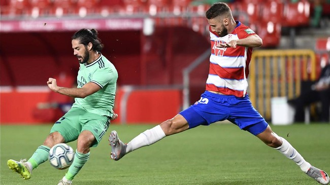 Real Madrid's Isco, left, duels for the ball with Granada's Domingos Duarte during the Spanish La Liga soccer match between Granada and Real Madrid at the Los Carmenes stadium in Granada, Spain, Monday, July 13, 2020. (AP Photo/Jose Breton)
