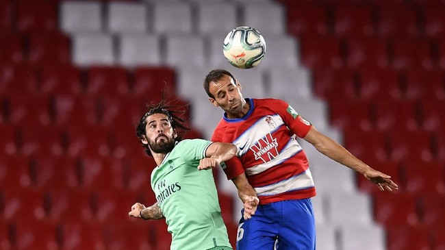 Real Madrid's Isco Alarcon, left, heads for the ball with Granada's German during the Spanish La Liga soccer match between Granada and Real Madrid at the Los Carmenes stadium in Granada, Spain, Monday, July 13, 2020. (AP Photo/Jose Breton)