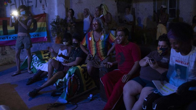 Indianara Siqueira, wearing a rainbow colored shirt, sits with fellow residents to watch their weekly presentations performed on a makeshift stage at the squat known as Casa Nem, occupied by members of the LGBTQ community who are in self-quarantine as a protective measure against the new coronavirus, in Rio de Janeiro, Brazil, Saturday, May 23, 2020. Siqueira, 49, a transgender sex worker and activist leads Casa Nem. (AP Photo/Silvia Izquierdo)
