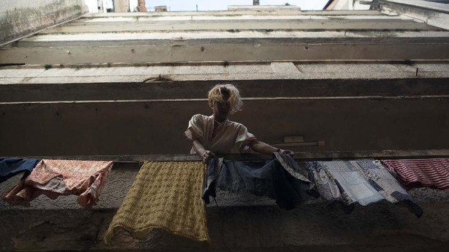Transgender Alex hangs clothes out to dry at the squat known as Casa Nem in Rio de Janeiro, Brazil, Wednesday, July 8, 2020. In 2016, members of the LGBTQ community led by Indianara Siqueira took over the balconied building with small bedrooms, shared bathrooms and a big common kitchen. (AP Photo/Silvia Izquierdo)