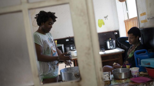 Morgana keeps Micaela company as she prepares rice balls for lunch in the kitchen of the squat known as Casa Nem, occupied by members of the LGBTQ community who are in self-quarantine as a protective measure against the new coronavirus, in Rio de Janeiro, Brazil, Wednesday, July 8, 2020. Self-imposed lockdown is one of few ways this traditionally marginalized group has found to minimize COVID-19 risks, while others remain vulnerable on the streets. (AP Photo/Silvia Izquierdo)