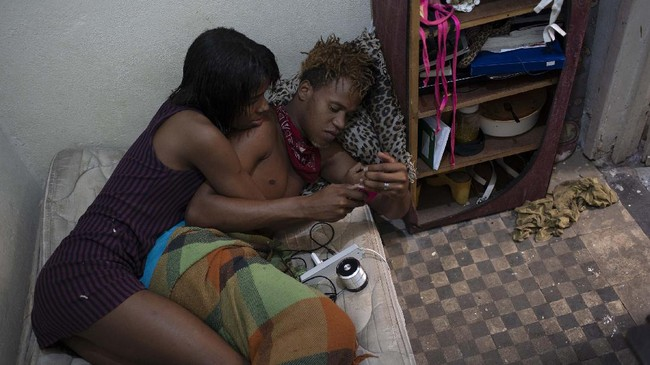 Transgender Klay Kardashian, left, and Marshall, listen to a voice message in Klay's room at the squat known as Casa Nem, occupied by members of the LGBTQ community who are in self-quarantine as a protective measure against the new coronavirus, in Rio de Janeiro, Brazil, Wednesday, July 8, 2020. (AP Photo/Silvia Izquierdo)