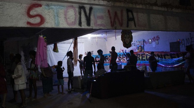 Members of the LGBTQ community gather in the courtyard of the squat known as Casa Nem to watch the weekly presentations by residents on a makeshift stage, in Rio de Janeiro, Brazil, Saturday, May 23, 2020.