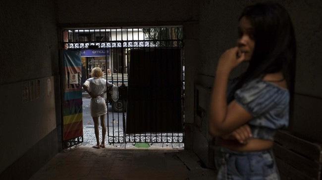 A resident of the squat Casa Nem waits at the entrance for a delivery of donated furniture, in Rio de Janeiro, Brazil, Wednesday, July 8, 2020. The six-floor building is home to members of the LGBTQ community riding out the pandemic behind closed doors. (AP Photo/Silvia Izquierdo)