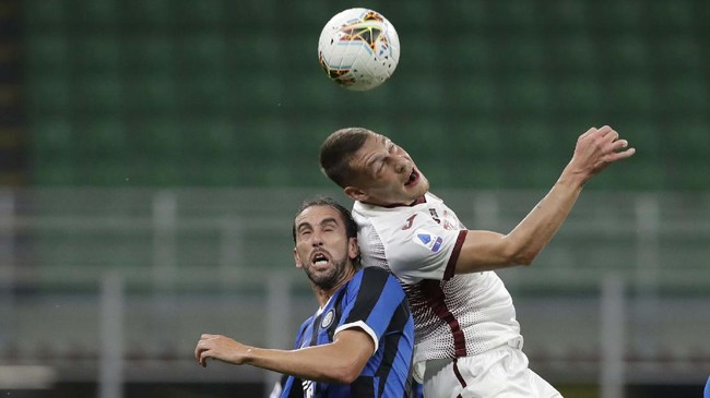 Inter Milan's Diego Godin, left, jumps for a header with Torino's Andrea Belotti during a Serie A soccer match between Inter Milan and Torino, at the San Siro stadium in Milan, Italy, Monday, July 13, 2020. (AP Photo/Luca Bruno