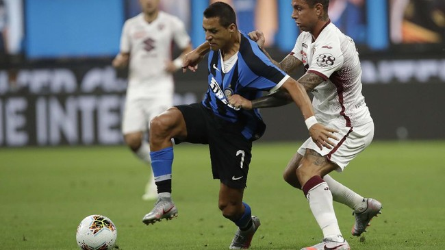 Inter Milan's Alexis Sanchez, left, fights for the ball with Torino's Armando Izzo during a Serie A soccer match between Inter Milan and Torino, at the San Siro stadium in Milan, Italy, Monday, July 13, 2020. (AP Photo/Luca Bruno