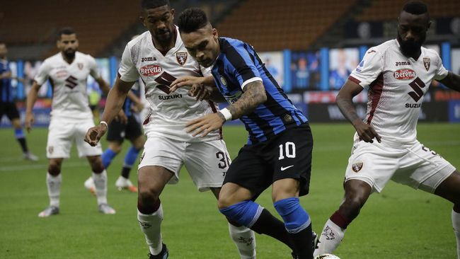 Inter Milan's Lautaro Martinez, center, fights for the ball with Torino's Gleison Bremer, left and Torino's Nicolas Nkoulou during a Serie A soccer match between Inter Milan and Torino, at the San Siro stadium in Milan, Italy, Monday, July 13, 2020. (AP Photo/Luca Bruno