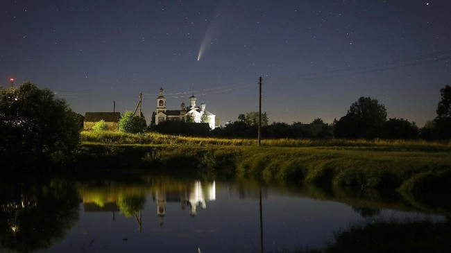 The comet Neowise or C/2020 F3 is seen before sunrise over the Turets, Belarus, 110 kilometers (69 miles) west of capital Minsk, early Tuesday, July 14, 2020. (AP Photo/Sergei Grits)