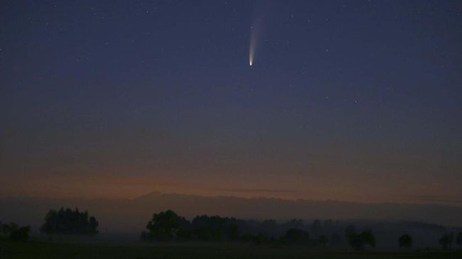 The comet Neowise or C/2020 F3 is be seen before sunrise over the Allg'u landscape, in Bad W'rishofen, Bavaria, Sunday, July 12, 2020.(Karl-Josef Hildenbrand/dpa via AP)