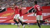 Manchester United's Anthony Martial, left, celebrates after scoring his ream's second goal during the English Premier League soccer match between Manchester United and Southampton at Old Trafford in Manchester, England, Monday, July 13, 2020. (AP Photo/Dave Thompson,Pool)