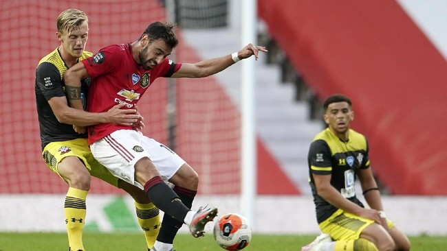 Manchester United's Bruno Fernandes kicks the ball as Southampton's James Ward-Prowse, left, watches during the English Premier League soccer match between Manchester United and Southampton at Old Trafford in Manchester, England, Monday, July 13, 2020. (AP Photo/Dave Thompson,Pool)