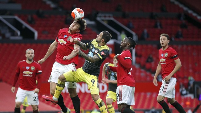 Manchester United's Harry Maguire, left, heads the ball as Southampton's Danny Ings watches during the English Premier League soccer match between Manchester United and Southampton at Old Trafford in Manchester, England, Monday, July 13, 2020. (AP Photo/Clive Brunskill,Pool)