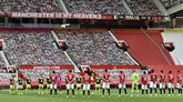 Players observe a minutes silence ahead of he English Premier League soccer match between Manchester United and Southampton at Old Trafford in Manchester, England, Monday, July 13, 2020. (AP Photo/Peter Powell,Pool)