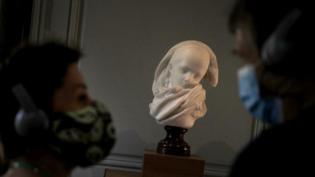 Visitor watch l'Orpheline Alsacienne by French sculptor Auguste Rodin in Paris Tuesday, July 7, 2020. The Musee Rodin is reopening this Tuesday morning albeit with a worrying loss of visitors and income caused by the four-months closure. Museum director, Catherine Chevillot, estimates the loss incurred by the crisis to be around 4.4 million euros (4.9 US dollars) and alleviated by the 1.4 million euro sales of bronze editions of Rodin statues. The museum doesn't sell Rodin statue originals but can sell 12 bronze replica editions of each of them, as it has been for 100 years. (AP Photo/Christophe Ena)