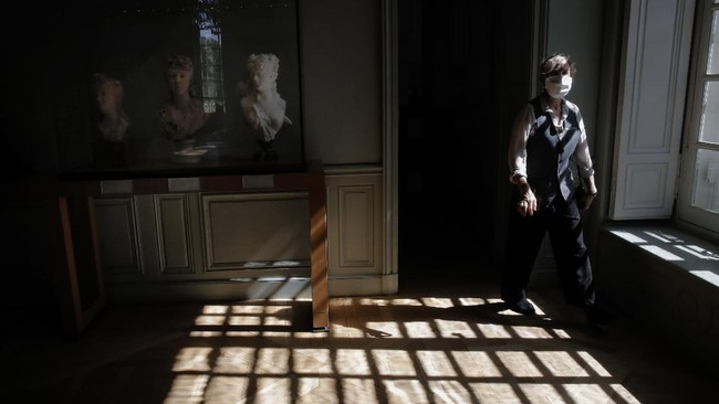 An employee walks past statues at the Rodin museum in Paris Tuesday, July 7, 2020. The Museum is reopening this morning albeit with a worrying loss of visitors and income caused by the four-months closure. Museum director, Catherine Chevillot, estimates the loss incurred by the crisis to be around 4.4 million euros (4.9 US dollars) and alleviated by the 1.4 million euro sales of bronze editions of Rodin statues. The museum doesn't sell Rodin statue originals but can sell 12 bronze replica editions of each of them, as it has been for 100 years. (AP Photo/Christophe Ena)