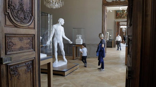 Travelers visit the Rodin museum in Paris Tuesday, July 7, 2020. The Musee Rodin is reopening this morning albeit with a worrying loss of visitors and income caused by the four-months closure. Museum director, Catherine Chevillot, estimates the loss incurred by the crisis to be around 4.4 million euros (4.9 US dollars) and alleviated by the 1.4 million euro sales of bronze editions of Rodin statues. The museum doesn't sell Rodin statue originals but can sell 12 bronze replica editions of each of them, as it has been for 100 years. (AP Photo/Christophe Ena)
