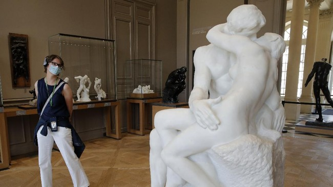 A visitor watches Le Baiser (The Kiss) by French sculptor Auguste Rodin in Paris Tuesday, July 7, 2020. The Musee Rodin is reopening this morning albeit with a worrying loss of visitors and income caused by the four-months closure. Museum director, Catherine Chevillot, estimates the loss incurred by the crisis to be around 4.4 million euros (4.9 US dollars). and alleviated by the 1.4 million euro sales of bronze editions of Rodin statues. The museum doesn't sell Rodin statue originals but can sell 12 bronze replica editions of each of them, as it has been for 100 years. (AP Photo/Christophe Ena)