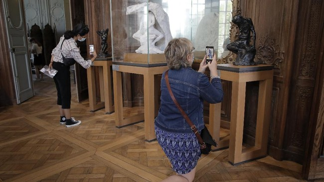 Visitors take pictures at the Rodin museum in Paris Tuesday, July 7, 2020. The Musee Rodin is reopening this morning albeit with a worrying loss of visitors and income caused by the four-months closure. Museum director, Catherine Chevillot, estimates the loss incurred by the crisis to be around 4.4 million euros (4.9 US dollars) and alleviated by the 1.4 million euro sales of bronze editions of Rodin statues. The museum doesn't sell Rodin statue originals but can sell 12 bronze replica editions of each of them, as it has been for 100 years. (AP Photo/Christophe Ena)
