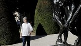 Rodin museum director Catherine Chevillot poses in the garden of Rodin museum in Paris Tuesday, July 7, 2020. The Musee Rodin is reopening this morning albeit with a worrying loss of visitors and income caused by the four-months closure. Catherine Chevillot, estimates the loss incurred by the crisis to be around 4.4 million euros (4.9 US dollars) and alleviated by the 1.4 million euro sales of bronze editions of Rodin statues. The museum doesn't sell Rodin statue originals but can sell 12 bronze replica editions of each of them, as it has been for 100 years. (AP Photo/Christophe Ena)