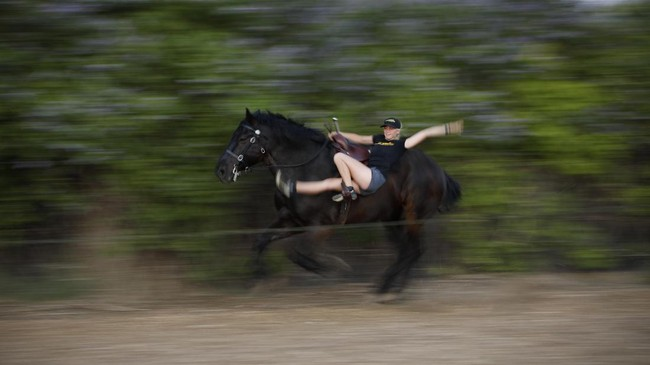 Ariel Hold practices a routine on a horse for