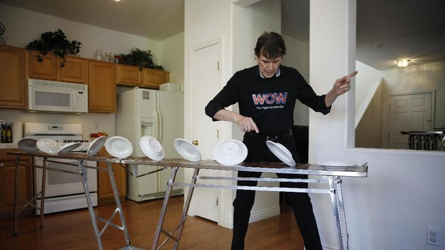 Juggler Victor Ponce practices his spinning plates routine in the kitchen of his home Friday, June 19, 2020, in Las Vegas. Ponce has continued to practice at home while the show he is in,
