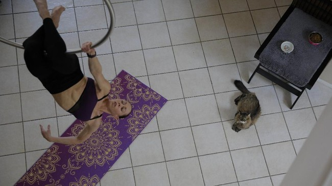 Johanna Sapakie, an aerialist, choreographer and dancer, trains in the living room of her home as her cat watches Sunday, June 21, 2020, in Las Vegas.