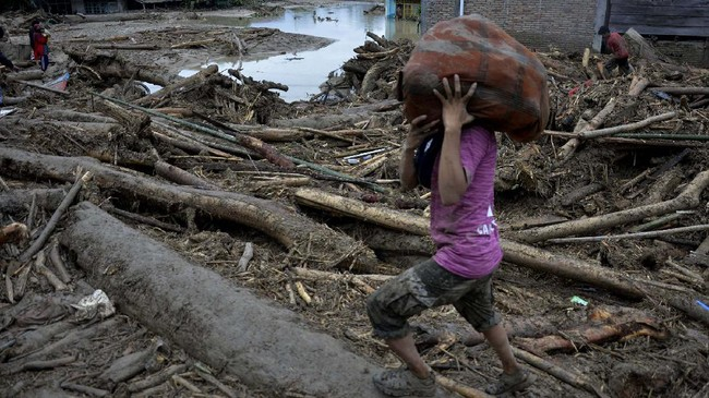 Warga menyelamatkan barang miliknya di sekitar rumah yang tertimbun lumpur dan batang pohon akibat terjangan banjir bandang di Kecamatan Masammba, Kabupaten Luwu Utara, Sulawesi Selatan, Rabu (15/7/2020). Banjir bandang yang terjadi akibat tingginya curah hujan tersebut mengakibatkan 16 orang meninggal dunia dan puluhan warga dilaporkan masih dalam pencarian, sementara ratusan rumah rusak berat dan hilang.ANTARA FOTO/Abriawan Abhe/aww.