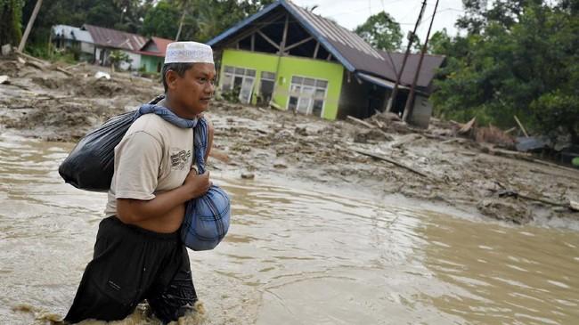 Warga berusaha menerobos banjir di Desa Radda, Kabupaten Luwu Utara, Sulawesi Selatan, Selasa (14/7/2020). Akibat banjir bandang tersebut mengakibatkan 10 orang meninggal dunia dan ratusan rumah tertimbun lumpur. ANTARA FOTO/Hariandi Hafid/yu/hp.