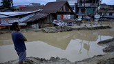 Warga memerhatikan rumah yang tertimbun lumpur akibat terjangan banjir bandang di Kecamatan Masammba, Kabupaten Luwu Utara, Sulawesi Selatan, Rabu (15/7/2020). Banjir bandang yang terjadi akibat tingginya curah hujan tersebut mengakibatkan 16 orang meninggal dunia dan puluhan warga dilaporkan masih dalam pencarian, sementara ratusan rumah rusak berat dan hilang.ANTARA FOTO/Abriawan Abhe/aww.