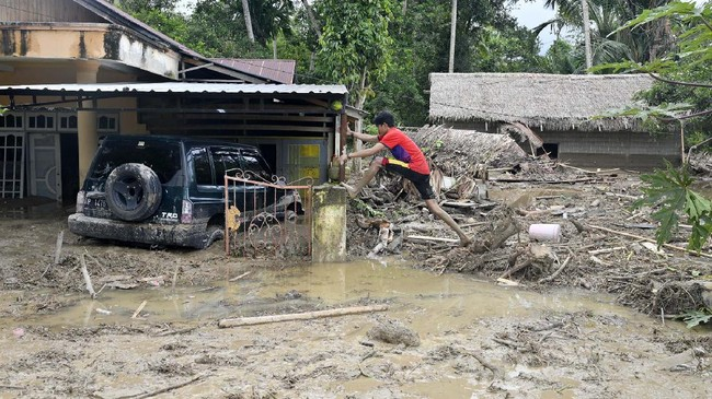 Warga berusaha memeanjat kedalam rumahnya yang tenggelam lumpur akibat banjir bandang di Desa Radda, Kabupaten Luwu Utara, Sulawesi Selatan, Selasa (14/7/2020). Akibat banjir bandang tersebut mengakibatkan 10 orang meninggal dunia dan ratusan rumah tertimbun lumpur. ANTARA FOTO/Hariandi Hafid/yu/hp.