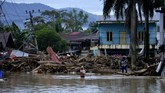 Warga melintas di sekitar rumah yang tertimbun lumpur dan batang pohon akibat terjangan banjir bandang di Kecamatan Masammba, Kabupaten Luwu Utara, Sulawesi Selatan, Rabu (15/7/2020). Banjir bandang yang terjadi akibat tingginya curah hujan tersebut mengakibatkan 16 orang meninggal dunia dan puluhan warga dilaporkan masih dalam pencarian, sementara ratusan rumah rusak berat dan hilang.ANTARA FOTO/Abriawan Abhe/aww.