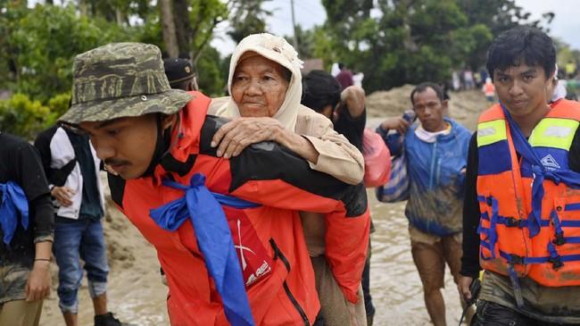 Tim SAR menggendong seorang korban banjir bandang saat dievakuasi di Desa Radda, Kabupaten Luwu Utara, Sulawesi Selatan, Selasa (14/7/2020). Akibat banjir bandang tersebut mengakibatkan 10 orang meninggal dunia dan ratusan rumah tertimbun lumpur. ANTARA FOTO/Hariandi Hafid/yu/hp.
