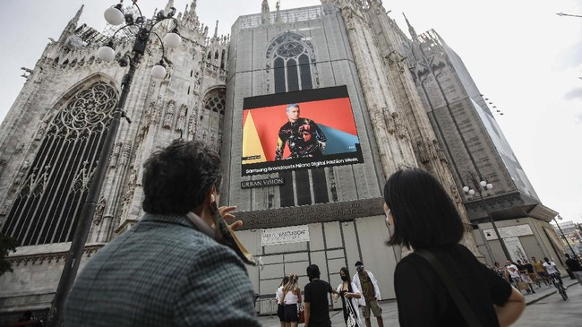 Pedestrians pass by a screen on the Duomo cathedral, showing a Moschino model during the Milan Digital Fashion Week, in Milan, Italy, Tuesday, July 14, 2020. Forty fashion houses are presenting previews of menswear looks for next spring and summer and pre-collections for women in digital formats, due to concerns generated by the COVID-19. (AP Photo/Luca Bruno)