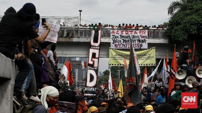 Kelompok buruh, petani, dan mahasiswa menolak Omnibus Law RUU Cipta Lapangan Kerja menggelar aksi di sisi kiri pintu gerbang DPR RI, Jakarta, Kamis (16/7). Pemerintah dan DPR dinilai gagal menangkap aspirasi masyarakat. CNN Indonesia/Andry Novelino