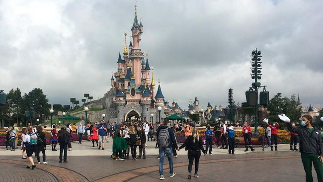Visitors and staff wearing protective face masks, walk down the Main Street of Disneyland Paris in Marne-la-Vallee, near Paris, on July 15, 2020, as Disneyland Paris begins phased reopening after months-closure aimed at stemming the spread of the novel coronavirus (COVID-19). (Photo by Aurelia MOUSSLY / AFP)