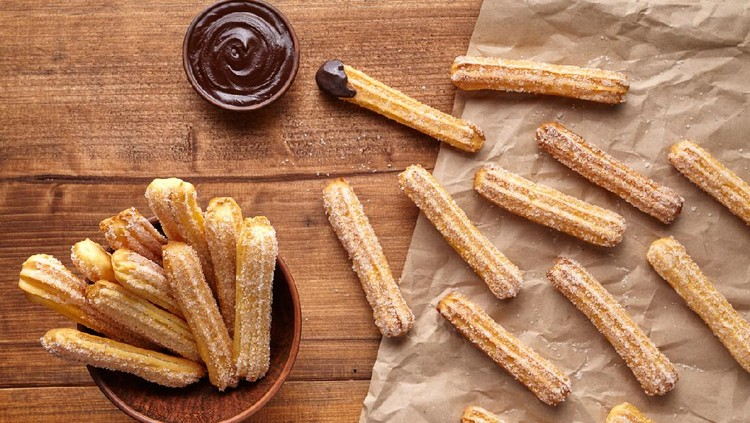 churros - Traditional Spanish and Mexican dessert on a white plate with chocolate sauce on an old grey rustic wooden table, horizontal view from above, close-up, flatlay