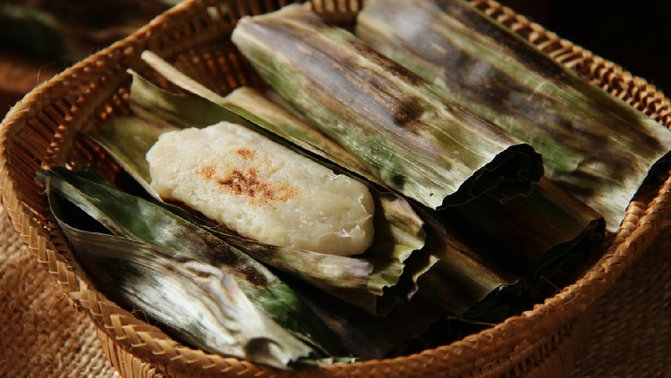 Otak-otak, the traditional snack of grilled fish cake from Jakarta. The fish cake is wrapped in banana leaf then grilled on a charcoal grill. The fish cakes are arranged on a bamboo basket with one of the cakes shown unwrapped.