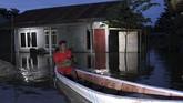 Warga melintas dengan menggunakan perahu di dekat rumahnya yang terendam banjir di Desa Lalonggotomi, Konawe, Sulawesi Tenggara, Rabu (15/7/2020). Luapan Sungai Konaweha mengakibatkan 1.669 jiwa mengungsi sementara 1.235 rumah terendam banjir yang tersebar di 11 Kecamatan di Kabupaten Konawe.  ANTARA FOTO/Jojon/foc.