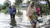 Warga berusaha menerobos banjir di Desa Lalonggotomi, Konawe, Sulawesi Tenggara, Rabu (15/7/2020). Luapan Sungai Konaweha mengakibatkan 1.669 jiwa mengungsi sementara 1.235 rumah terendam banjir yang tersebar di 11 Kecamatan di Kabupaten Konawe.  ANTARA FOTO/Jojon/foc.