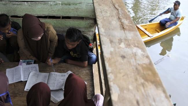 Siswa SD Negeri 1 Praja Taman Sari mengikuti pelajaran di salah satu rumah warga di Desa Laloika, Konawe, Sulawesi Tenggara, Selasa (14/7/2020). Pihak sekolah terpaksa  memberlakukan belajar kelompok bagi muridnya yang terdampak banjir. ANTARA FOTO/Jojon/foc.