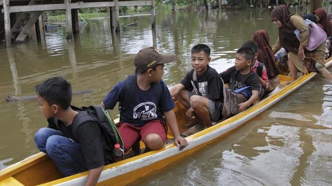 Siswa SD Negeri 1 Praja Taman Sari diatas rakit untuk belajaran di salah satu rumah warga di Desa Laloika, Konawe, Sulawesi Tenggara, Selasa (14/7/2020). Pihak sekolah terpaksa  memberlakukan belajar kelompok bagi muridnya yang terdampak banjir. ANTARA FOTO/Jojon/foc.