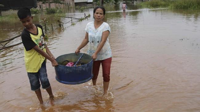 Warga mengangkat barang dari rumahnya yang terendam banjir di Desa Laloika, Kecamatan Pondidaha, Konawe, Sulawesi Tenggara, Senin (13/7/2020). Banjir yang melanda Desa Laloika dan Desa Wonuamonapa sejak pekan lalu tersebut diakibatkan meluapnya Sungai Konaweha sehingga 106 rumah warga terendam banjir dan 354 warga mengungsi. ANTARA FOTO/Jojon/wsj.